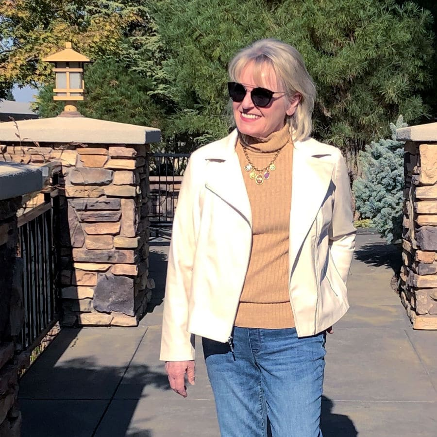 jennifer of well styled life wearing camel colored turtleneck, cream colored jacket and sunglasses