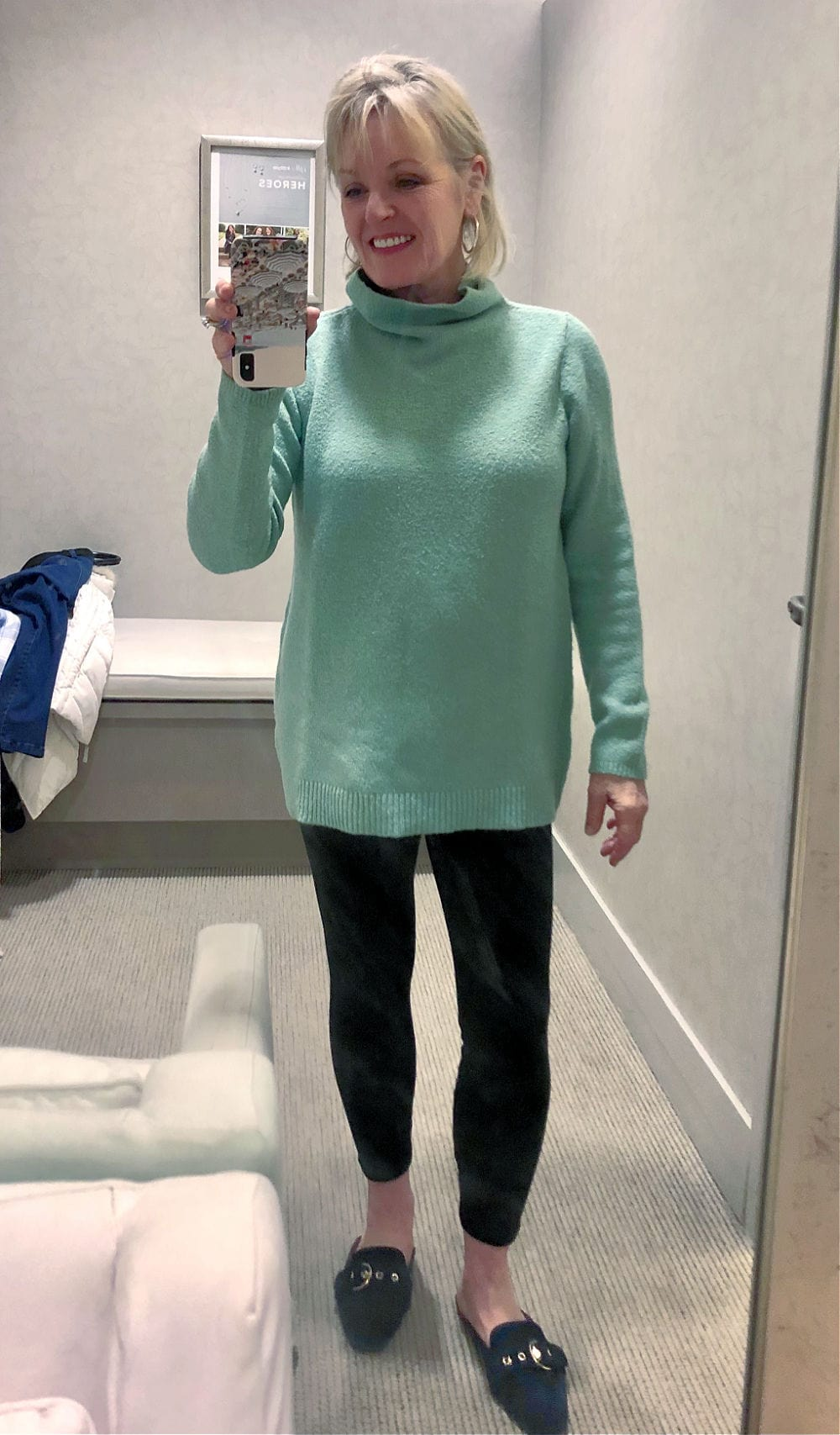 jennifer of a well styled life in j jill dressing room wearing aqua sweater and velvet leggings