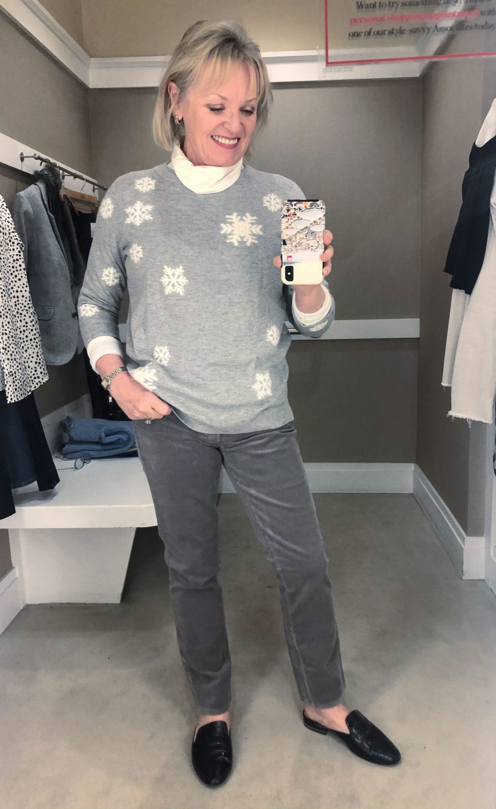jennifer of a well styled life wearing snowflake sweater and grey corduroy pants in talbots dressing room