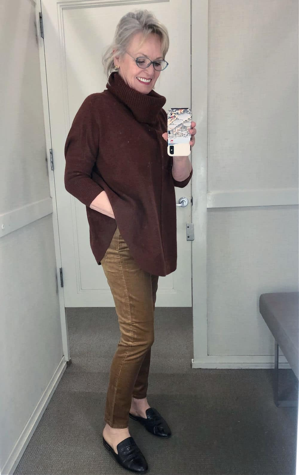 fashion blogger jennifer of a well styled life in Loft dressing room wearing cords and sweater poncho