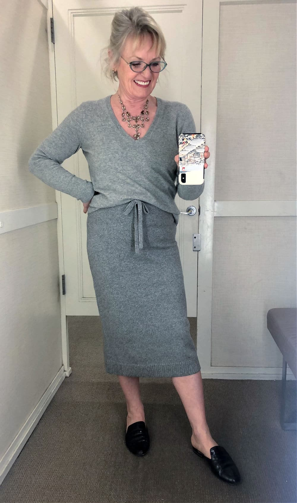 jennifer of a well styled life trying on gray sweater skirt at loft