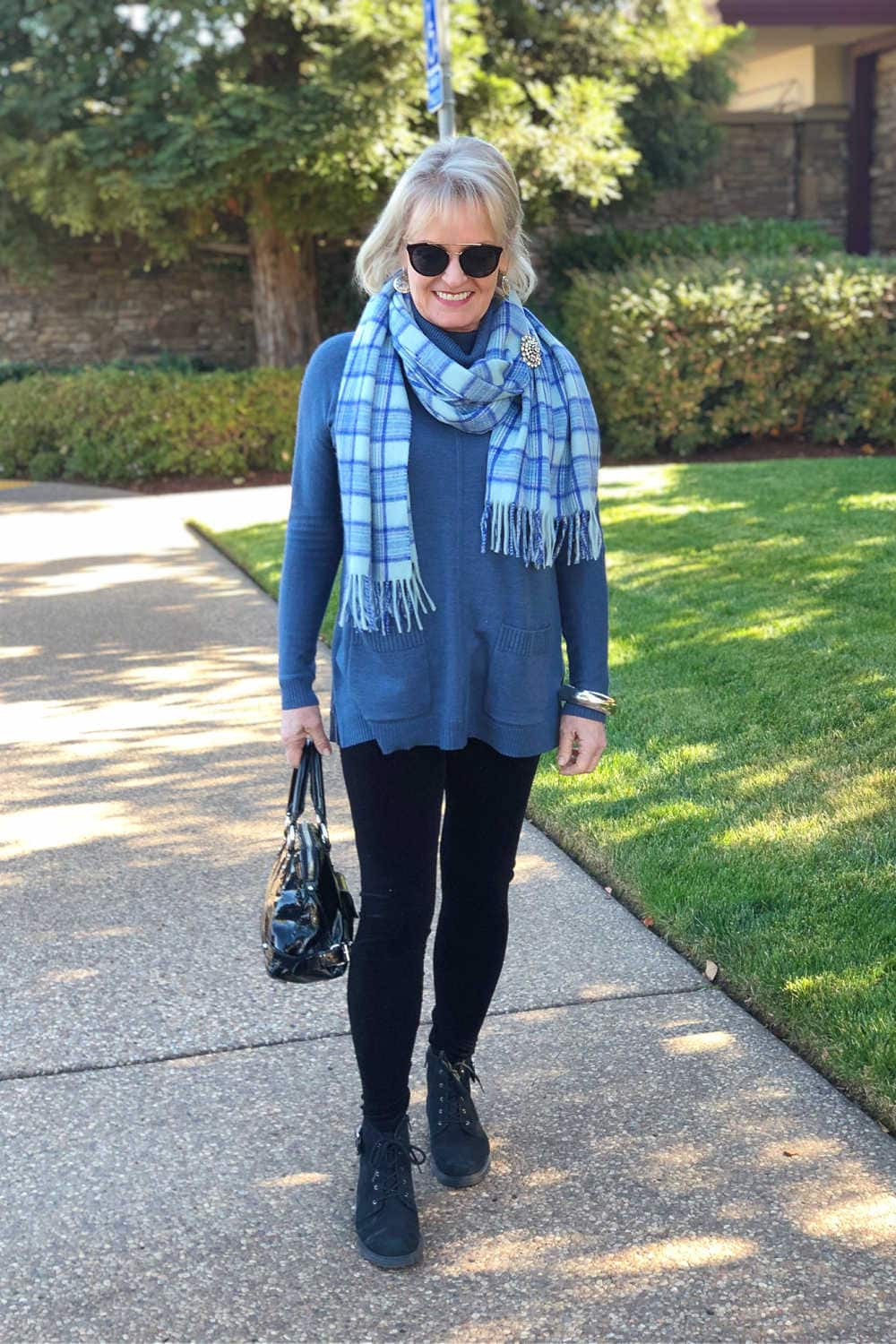 fashion blogger jennifer of a well styled life wearing casual holiday outfit with velvet leggings, tunic sweater and booties