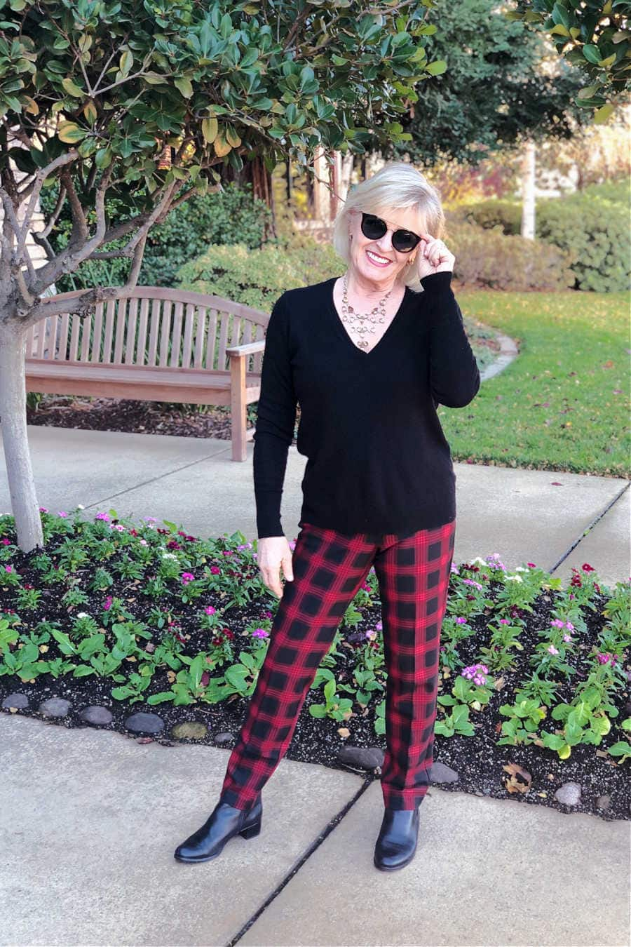 over 50 fashion blogger jennifer conolly of a well styled life wearing black and red checked pants and black sweater