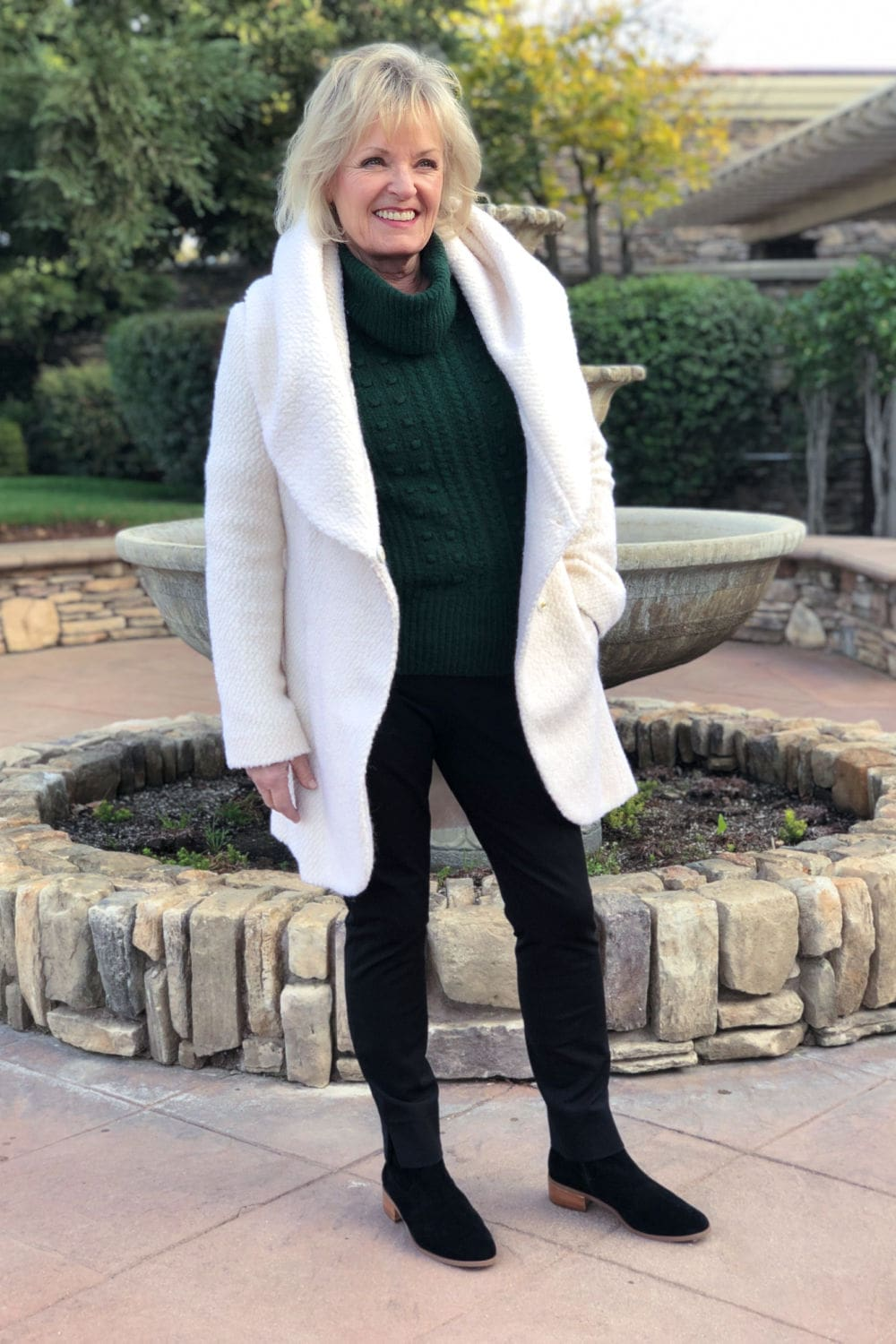 jennifer of a well styled life wearing ivory coat over green sweater and navy pants from Nordstrom