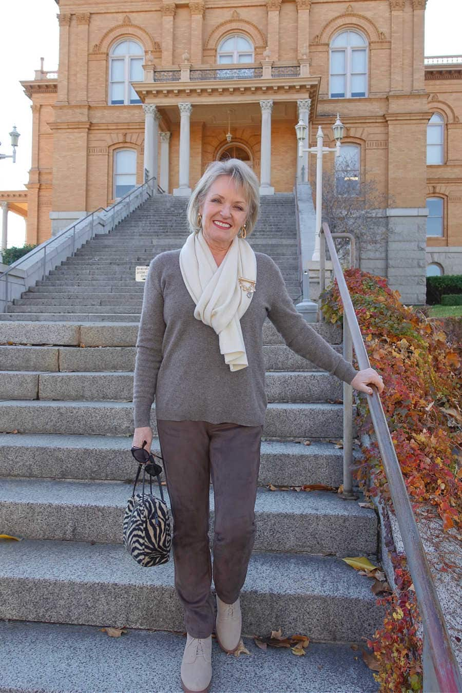 jennifer connolly of a well styled life wearing beige sweater and pants on stairs of old building