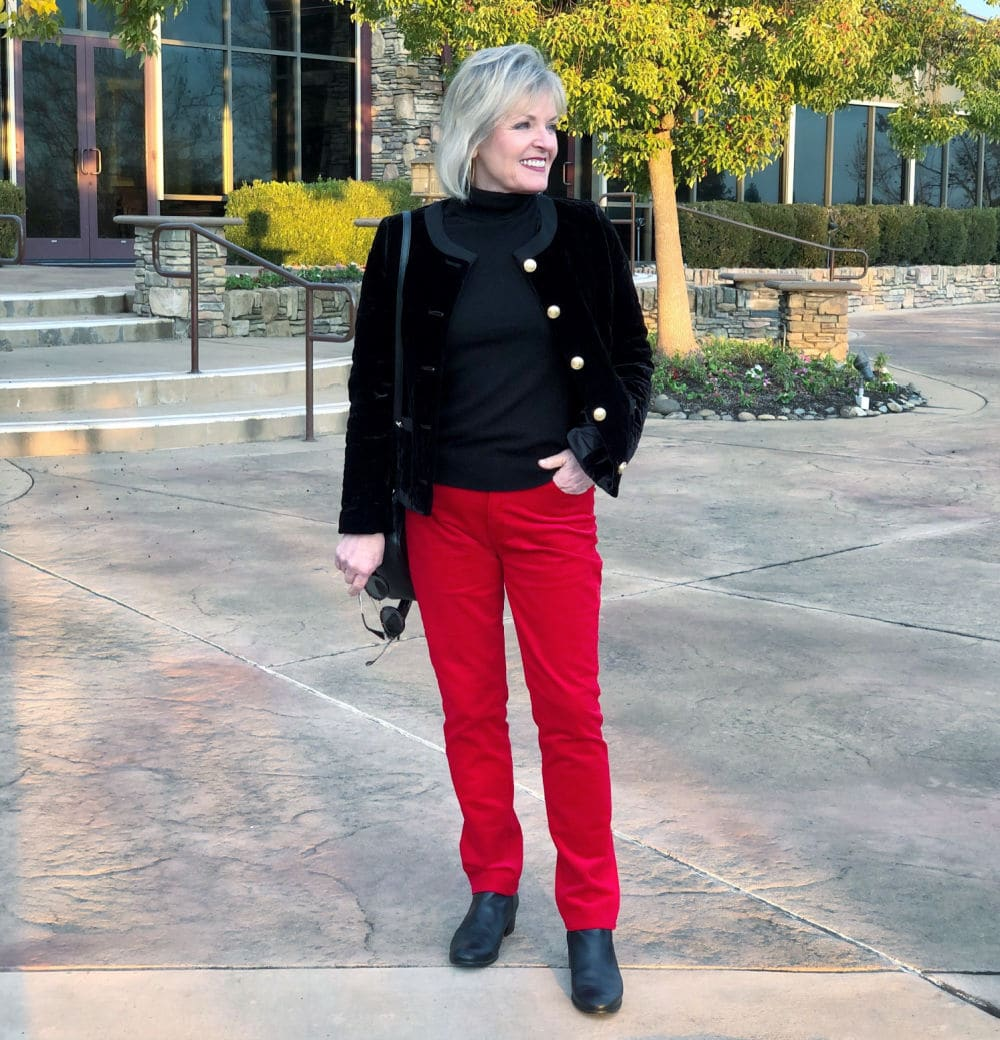fashion blogger jennifer connolly of a well styled life modeling black jaket over red pants