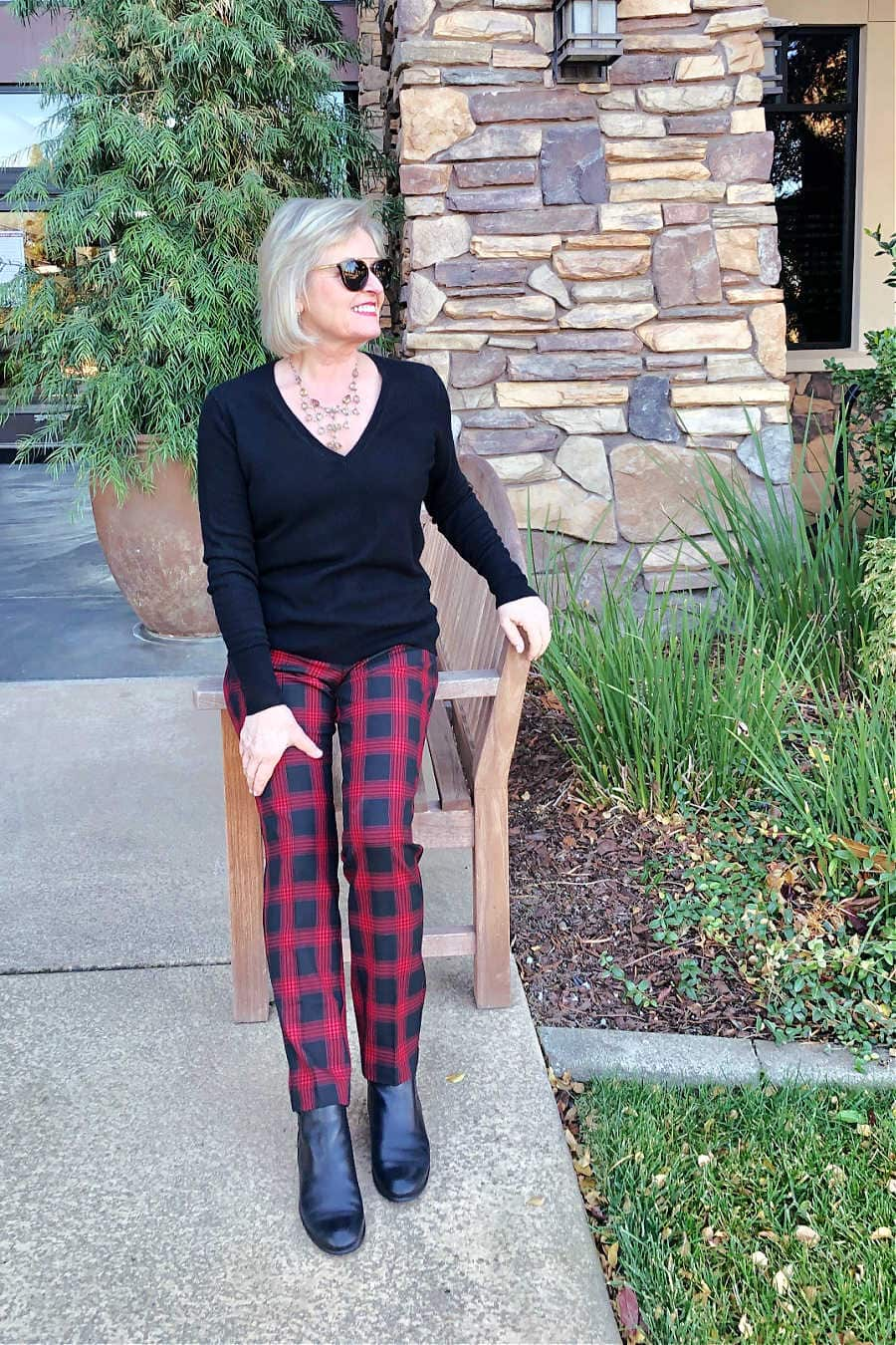 fashion blogger jennifer of a well styled life wearing everlane black sweater with red and black check pants from j jill