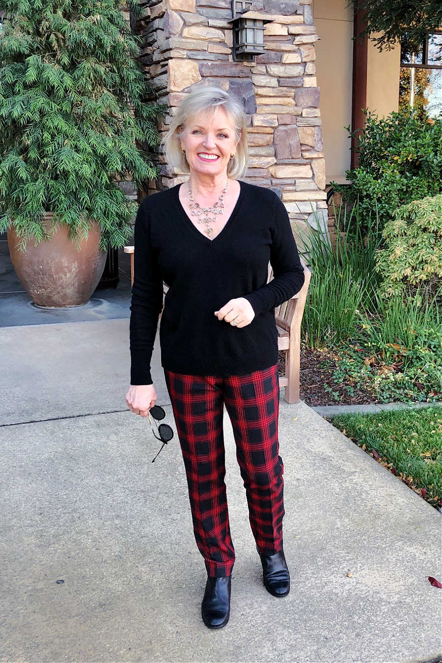 over 50 fashion blogger jennifer connolly of a well styled life wearing everlane black sweater with red and black checked pants from j jill