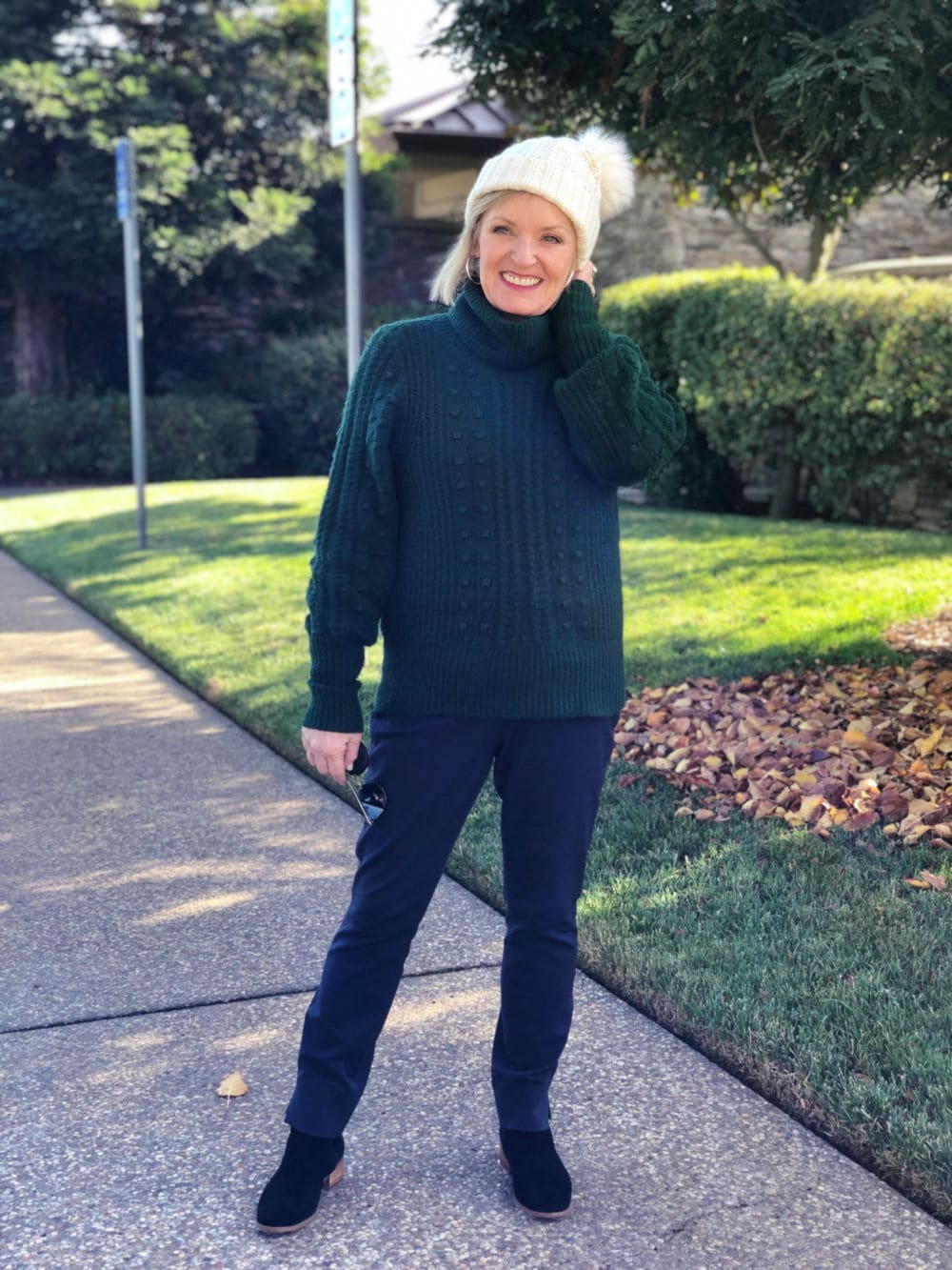 green sweater, navy pants, and black booties on jennifer of a well styled life