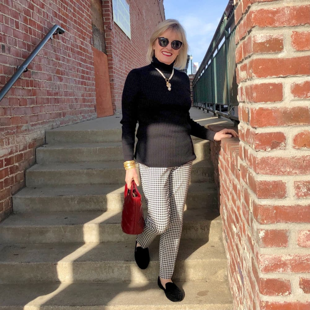 jennifer connolly of a well styled life wearing black and white houndtooth pants with black sweater and red handbag