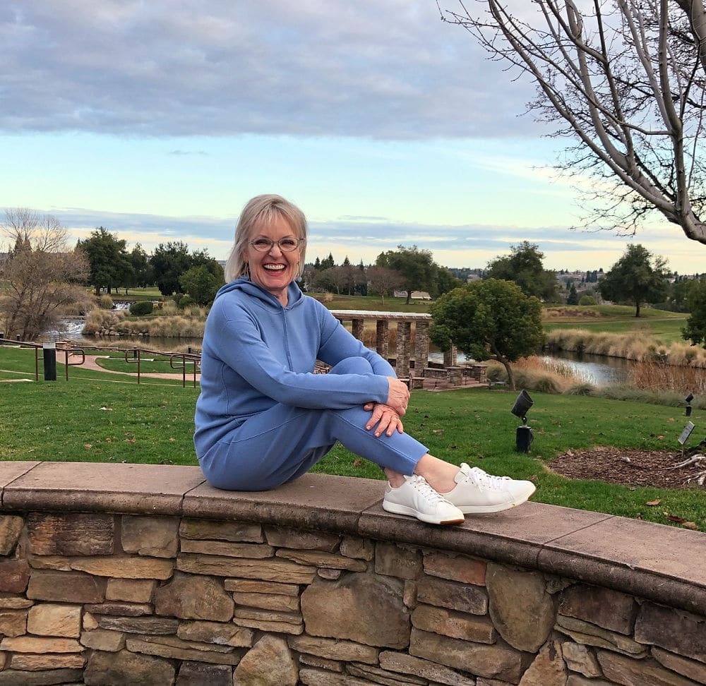 over 50 fashion blogger jennifer connolly of a well styled life wearing blue hoodie and blue sweater pants with white sneakers