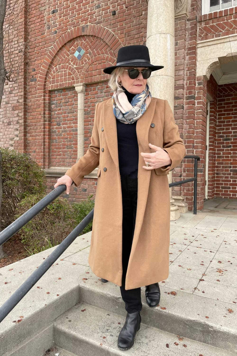 camel coat over black sweater, jeans and boots on Jennifer or a well styled life