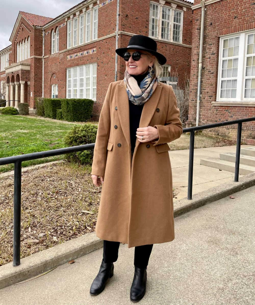 woman wearing camel coat over black turtle neck and jeans with black hat