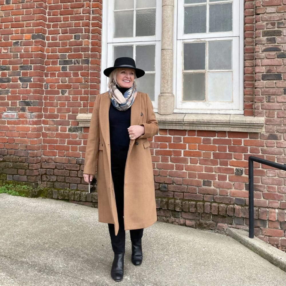 jennifer of a well styled life wearing camel coat, black jeans, navy turtleneck and black hat