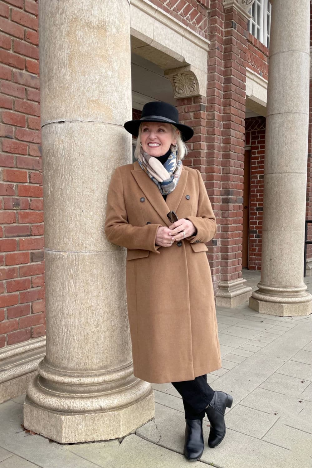 woman leaning against column wearing camel coat and black hat