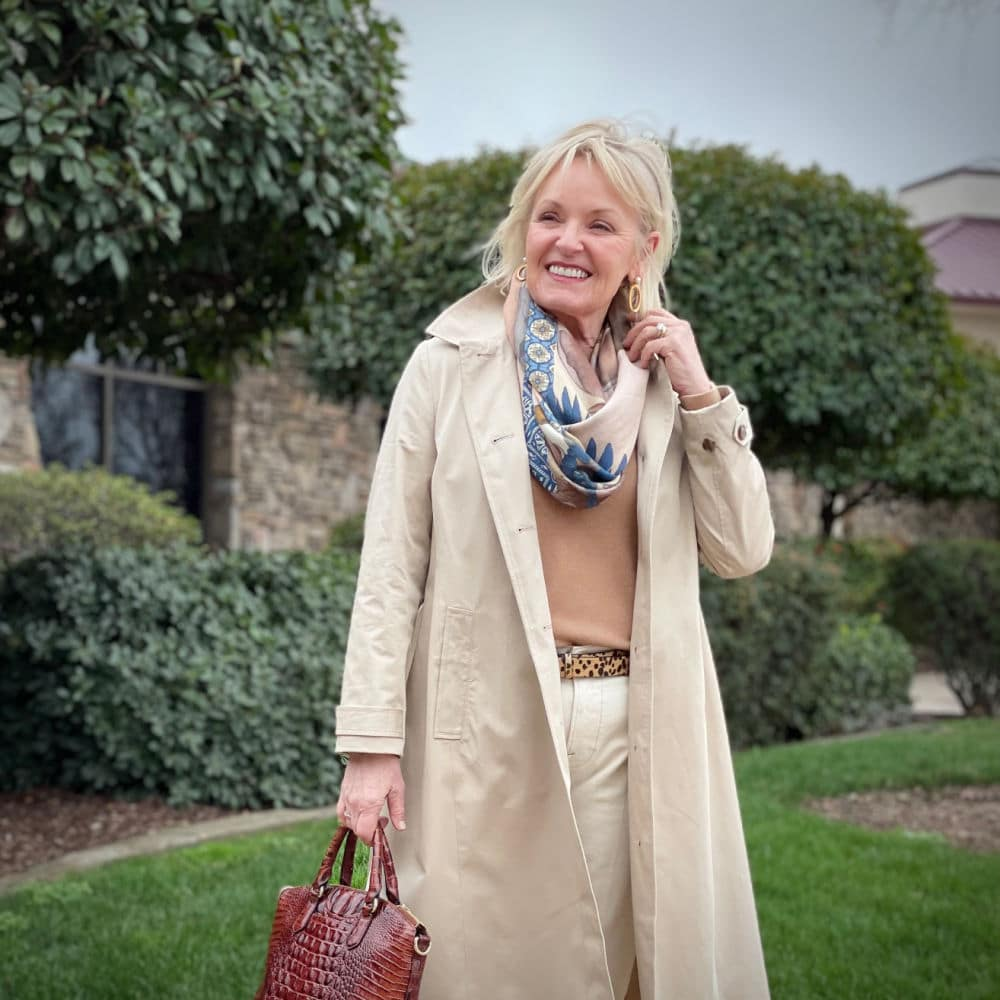 blonde woman wearing trench coat over camel sweater and cream colored jeans with colorful scarf