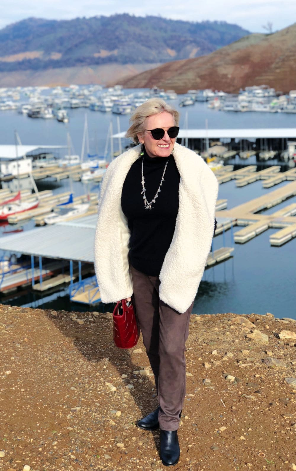 over 50 fashion blogger jennifer connolly of a well styled life wearing teddy bear vest and faux suede pants standing on bluff overlooking lake oroville
