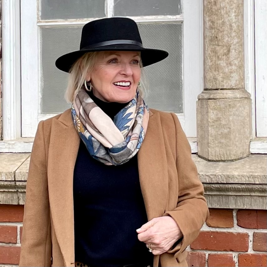 woman in black hat with scarf and camel coat