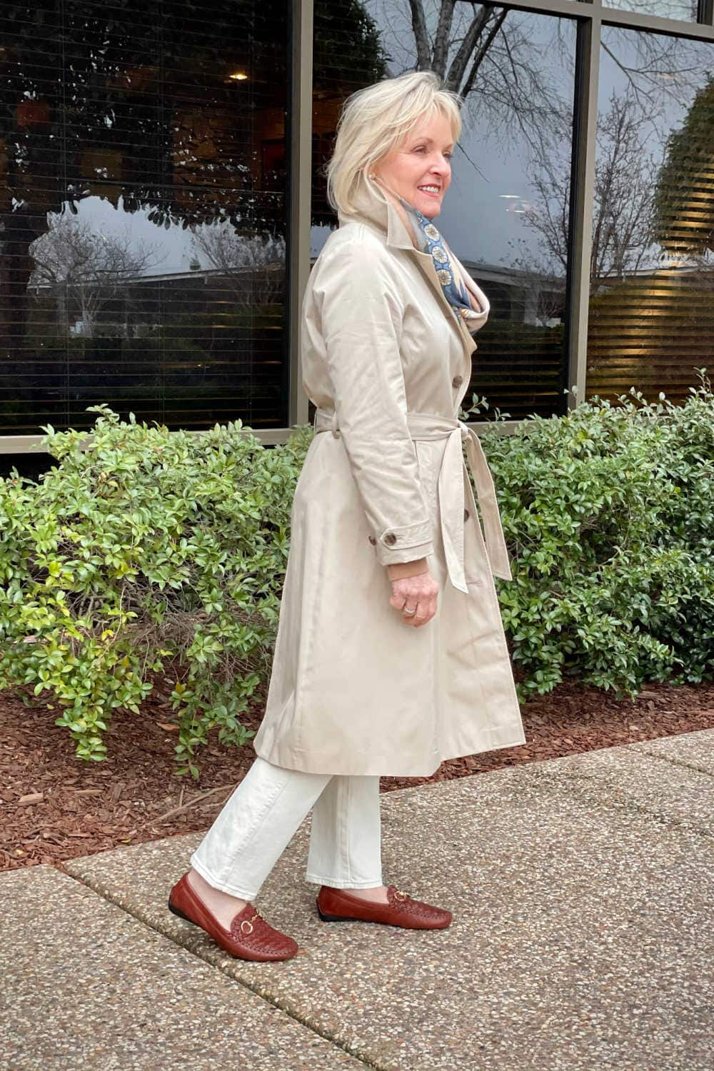 woman wearing pale khaki trench coat from Loft over pale beige jeans and bronw driving mocs