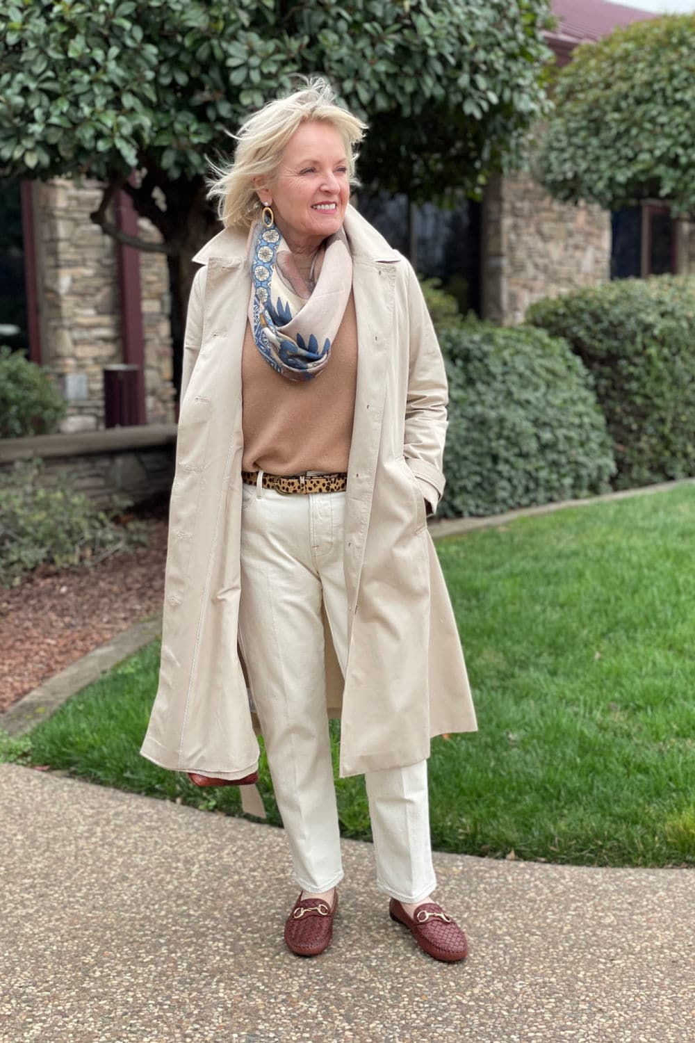 jennifer of a well styled life wearing loft swing trench coat over camel colored sweater and ivory jeans