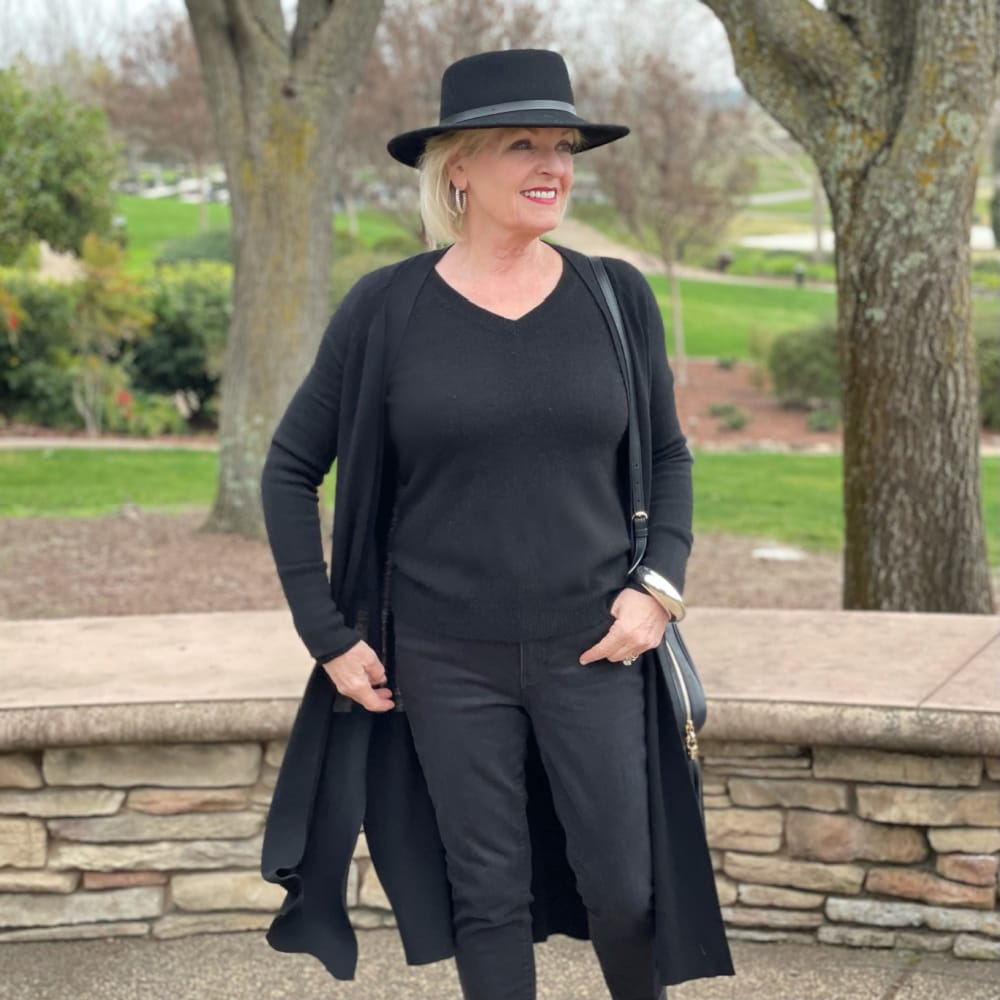 woman wearing black hat and black v neck with black jeans