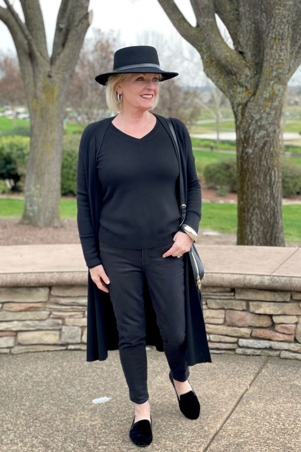 over 50 woman wearing black hat, black sweater and jeans