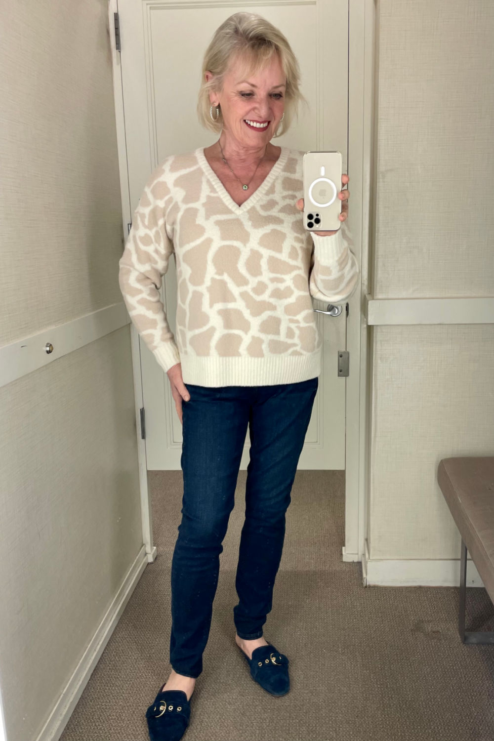 animal print sweater and deep blue jeans on woman in dressing room