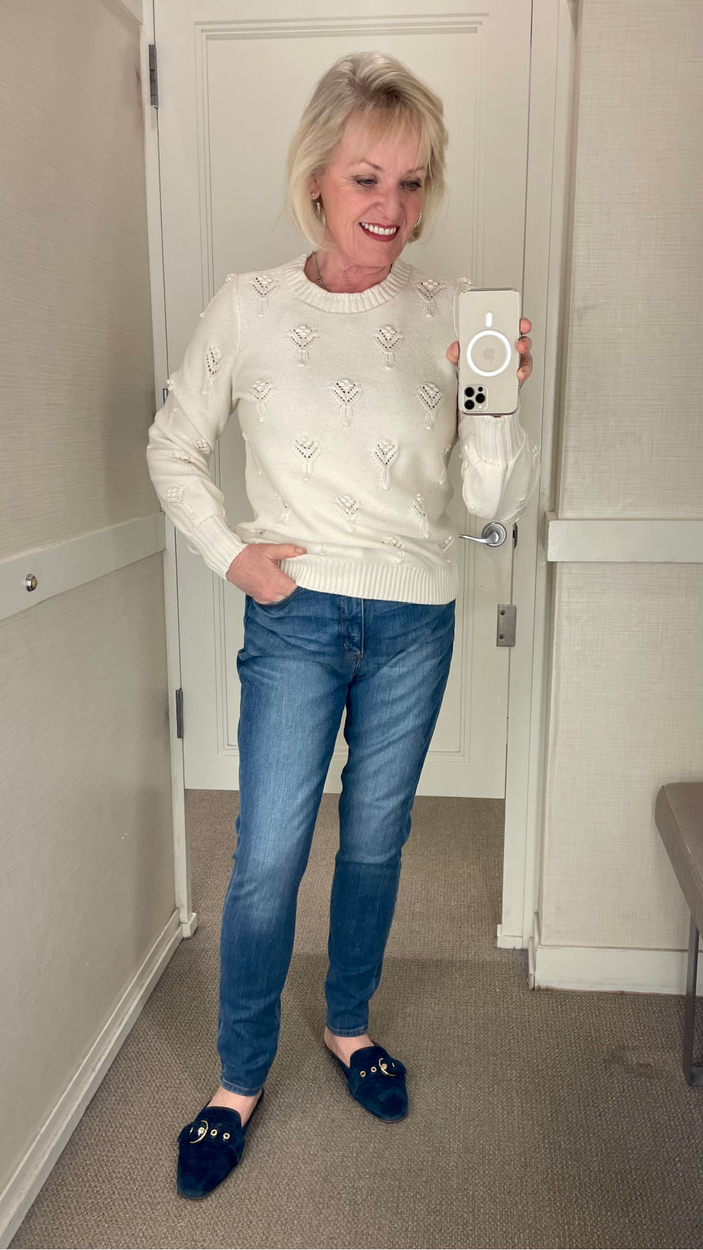 middle age woman wear off white sweater a pale blue jeans in dressing room