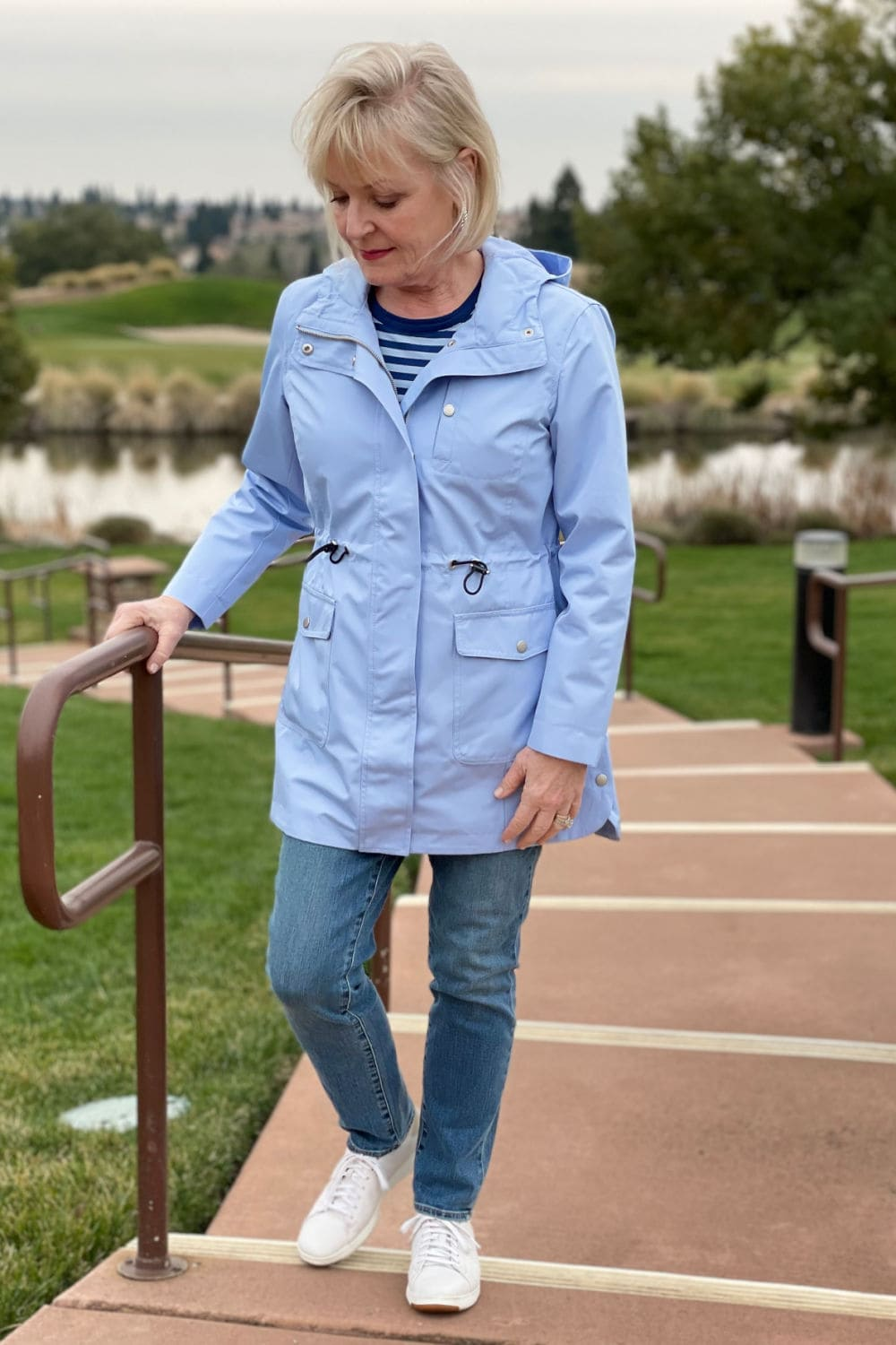 woman walking up the stairs in blue anorak and blue jeans