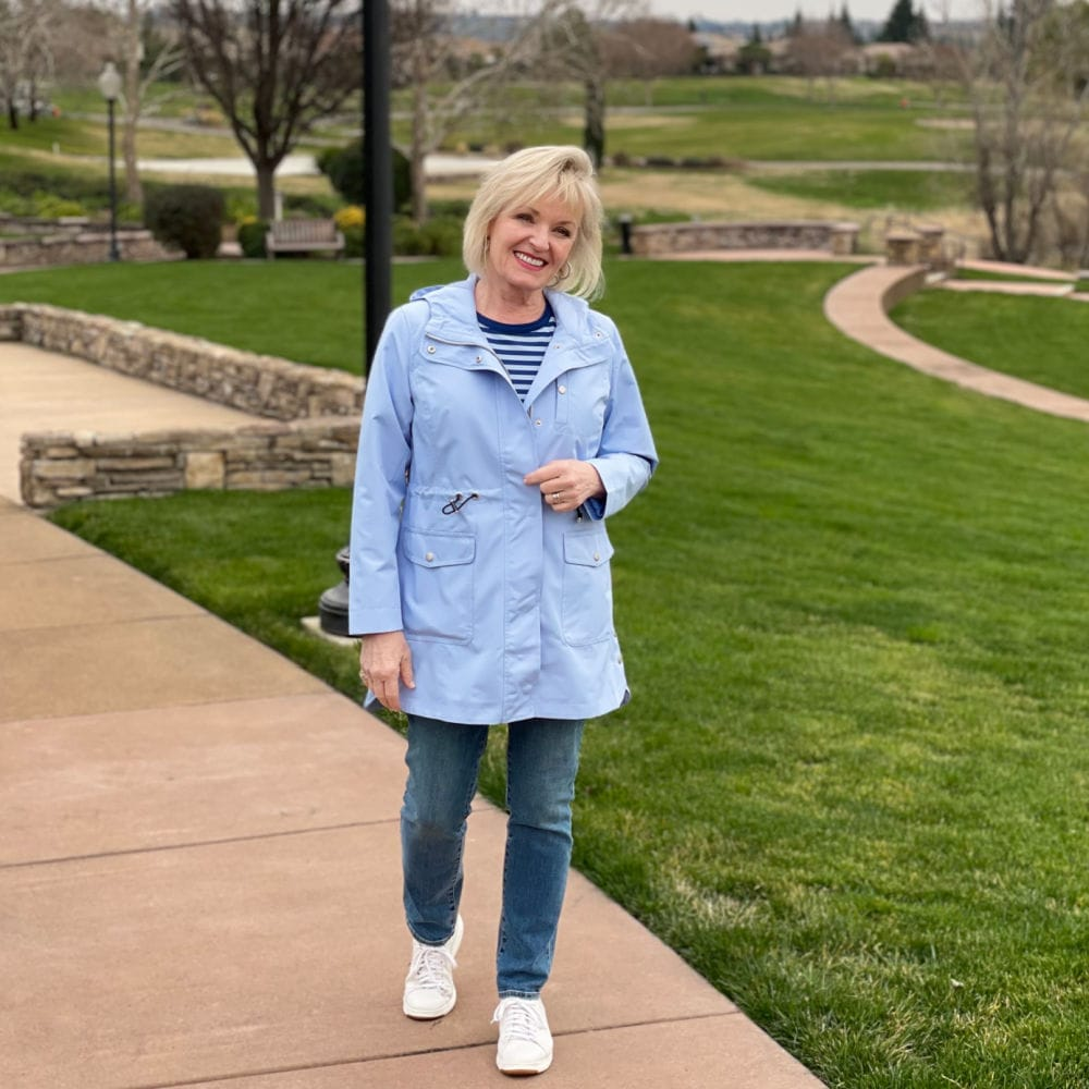blonde woman wearing blueanorak jacket with blue jeans and striped tee shirt on gold course path
