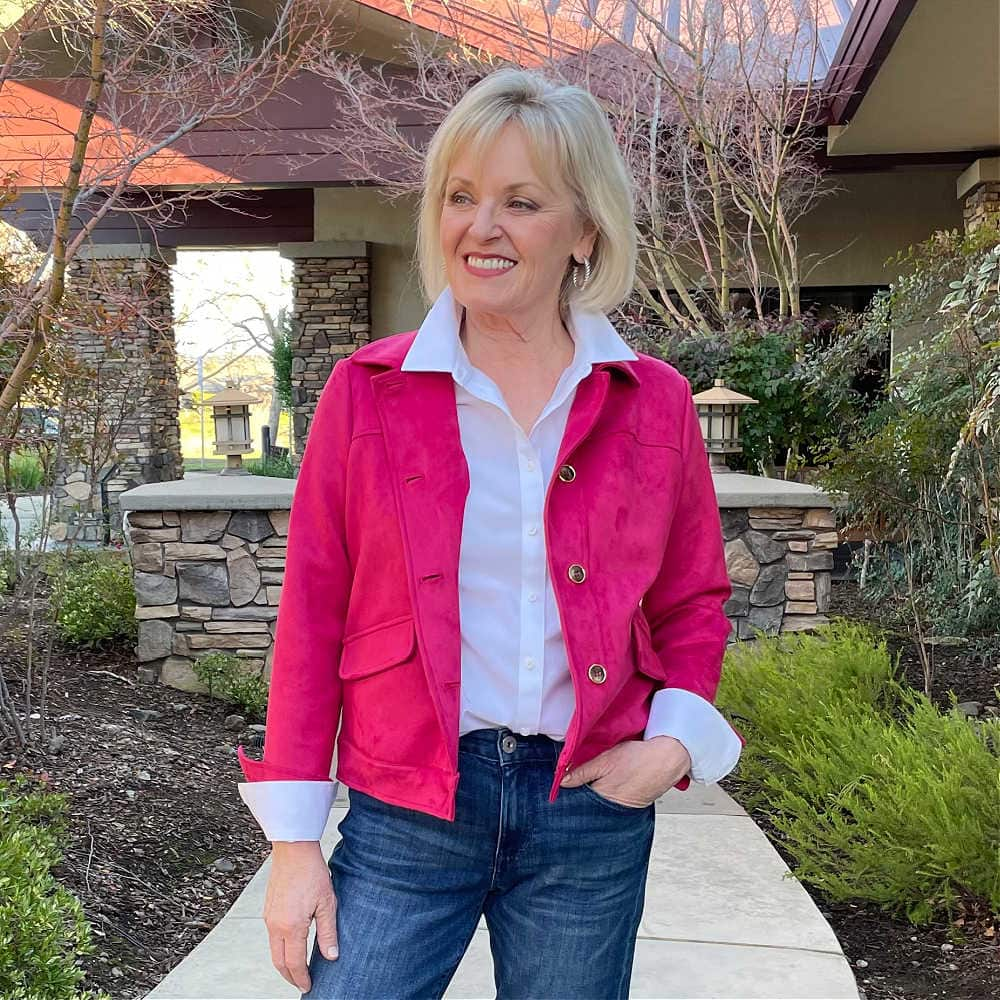 fashion blogger jennifer of a well styled life wearing raspberry fauz suede jacket over white shirt and blue jeans