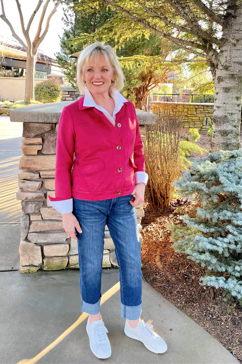 woman wearing white shhirt, bright pink jacket and blue jeans