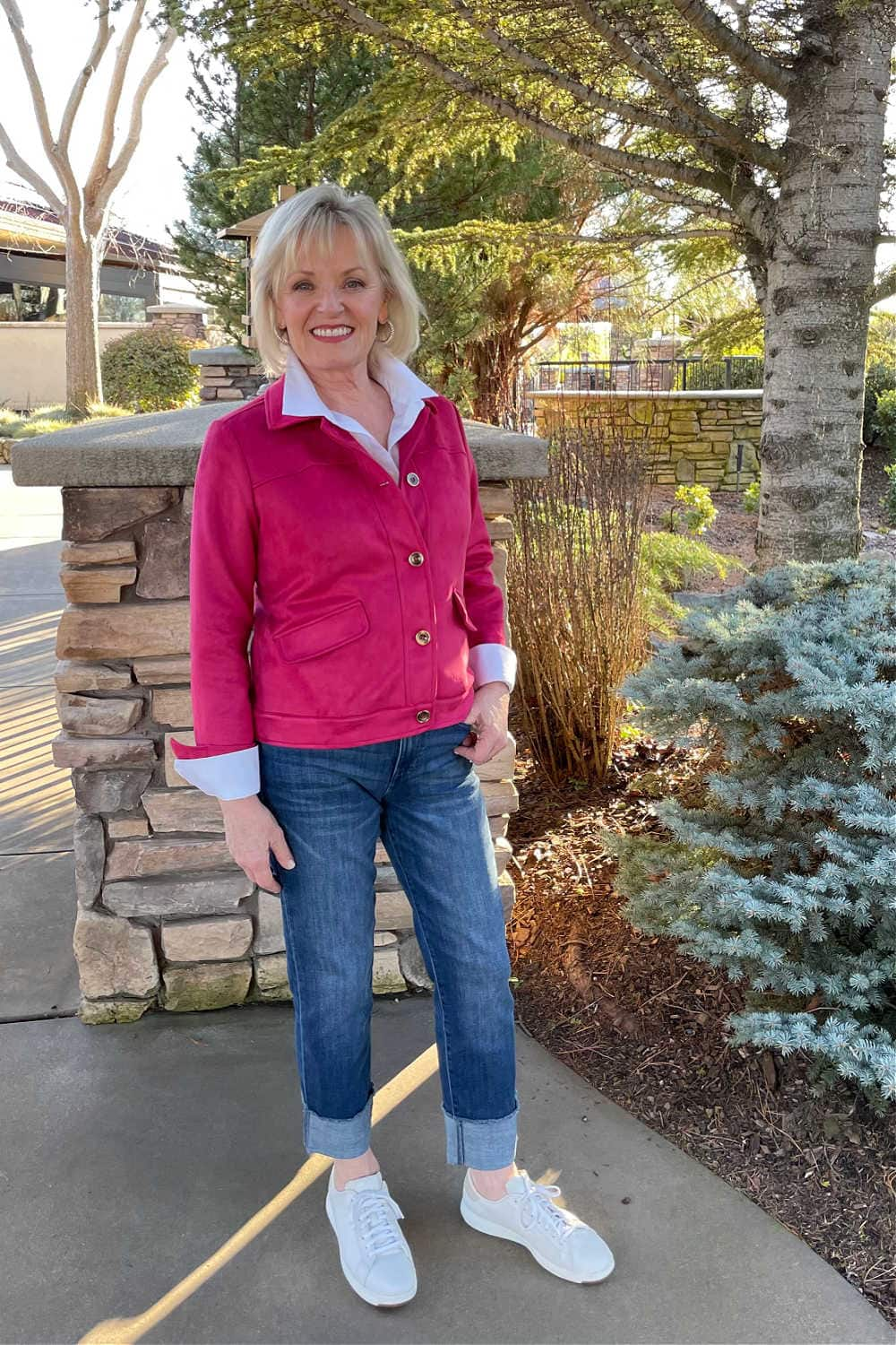 woman wearing pink jacket, white shirt, cuffed jeans and white sneakers