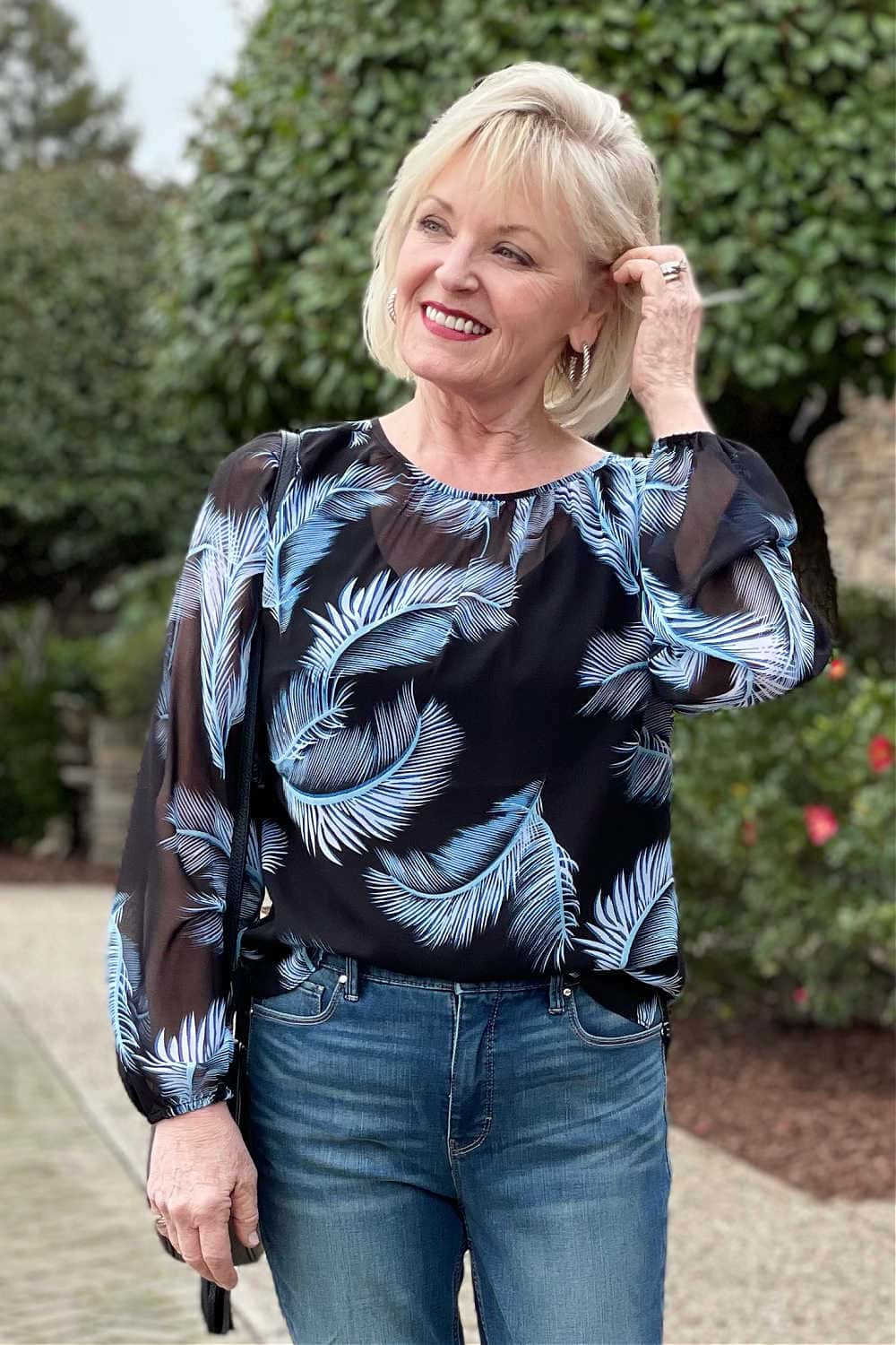 over 50 woman wearing sheer blouse with feather pattern