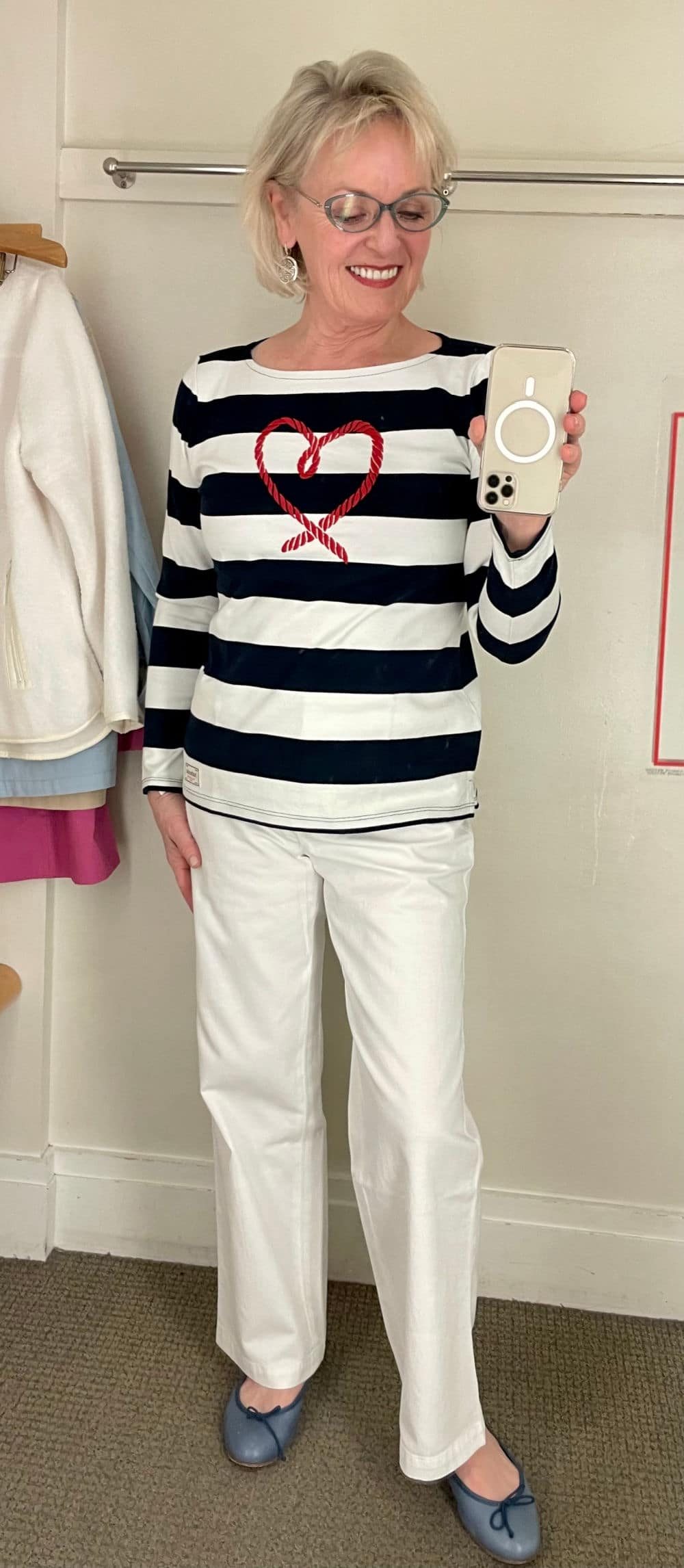 blonde woman modeling striped tee in dressing room