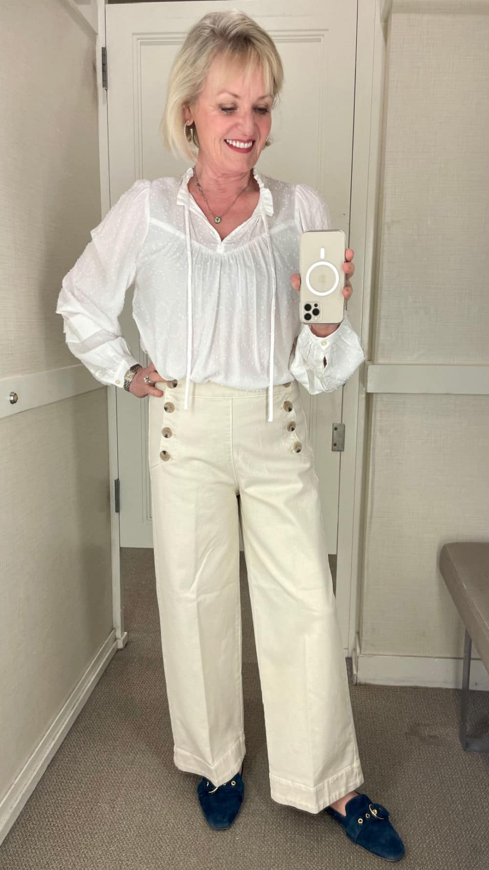 over 50 fashion blogger wearing sailor wide-leg pants and white blouse in dressing room