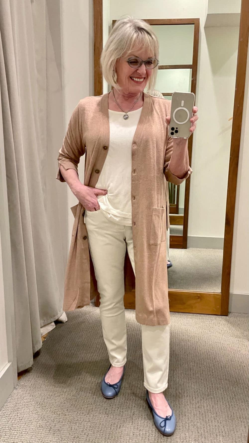 woman wearing long beige cardigan over beige tank top and jeans in J Jill dressing room