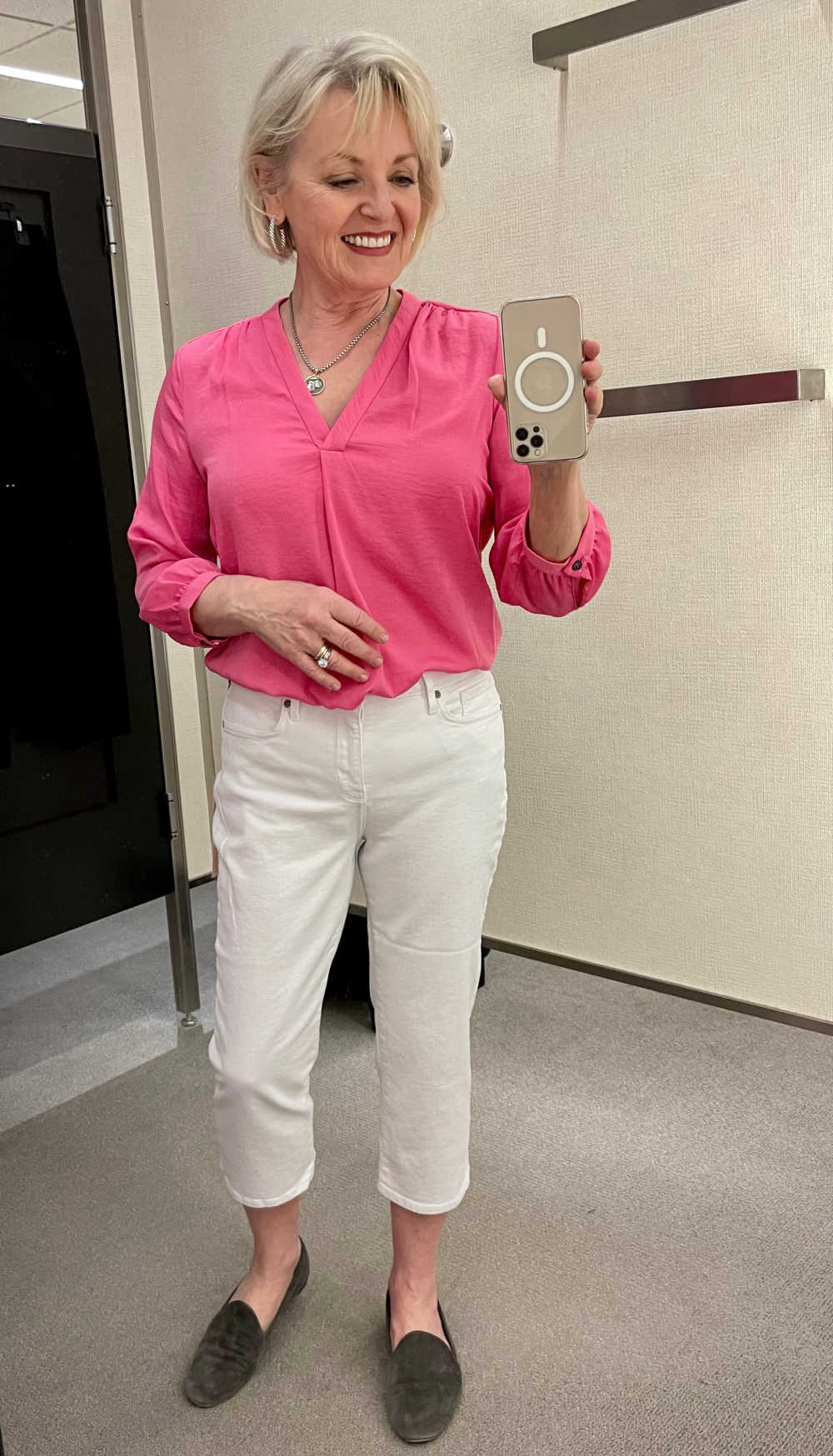 blonde woman wearing pink blouse and white crop pants