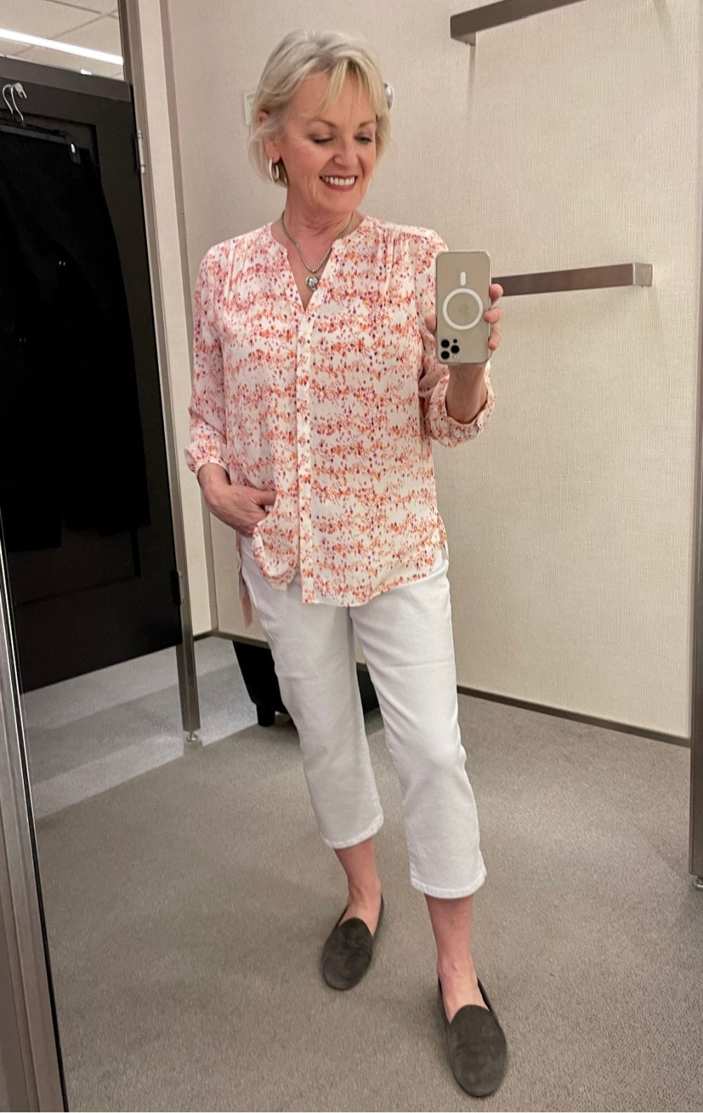 WOMAN IN DRESSING ROOM WEARING PINK VINCE BLOUSE AND WHITE CROPS