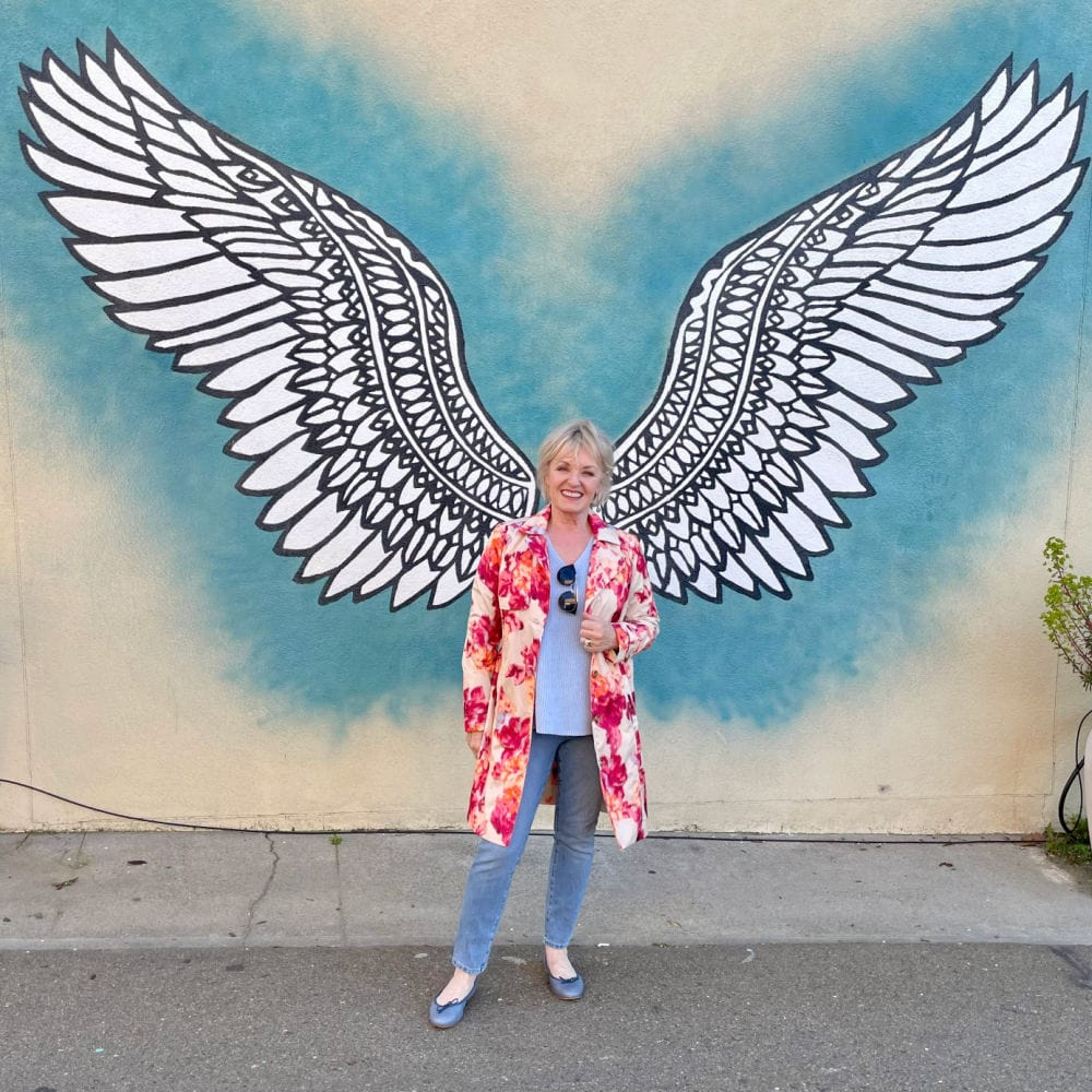 woman standing in front of angel mural wearing floral trench coat