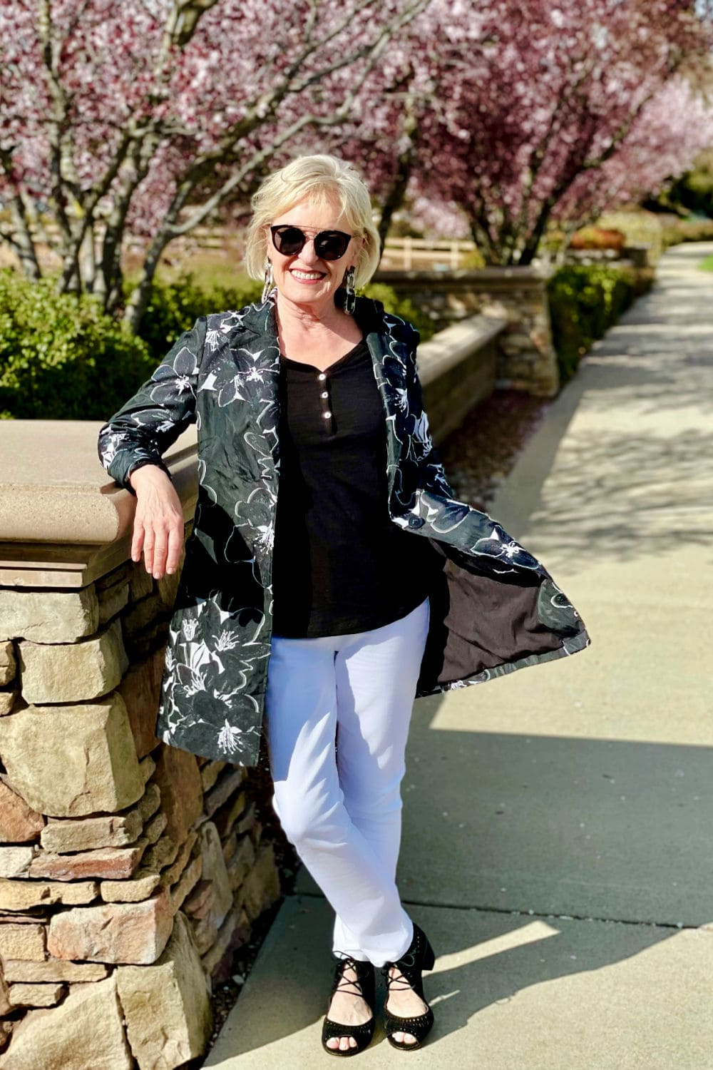 over 50 fashion blogger wearing black top, white jeans and leaning against wall