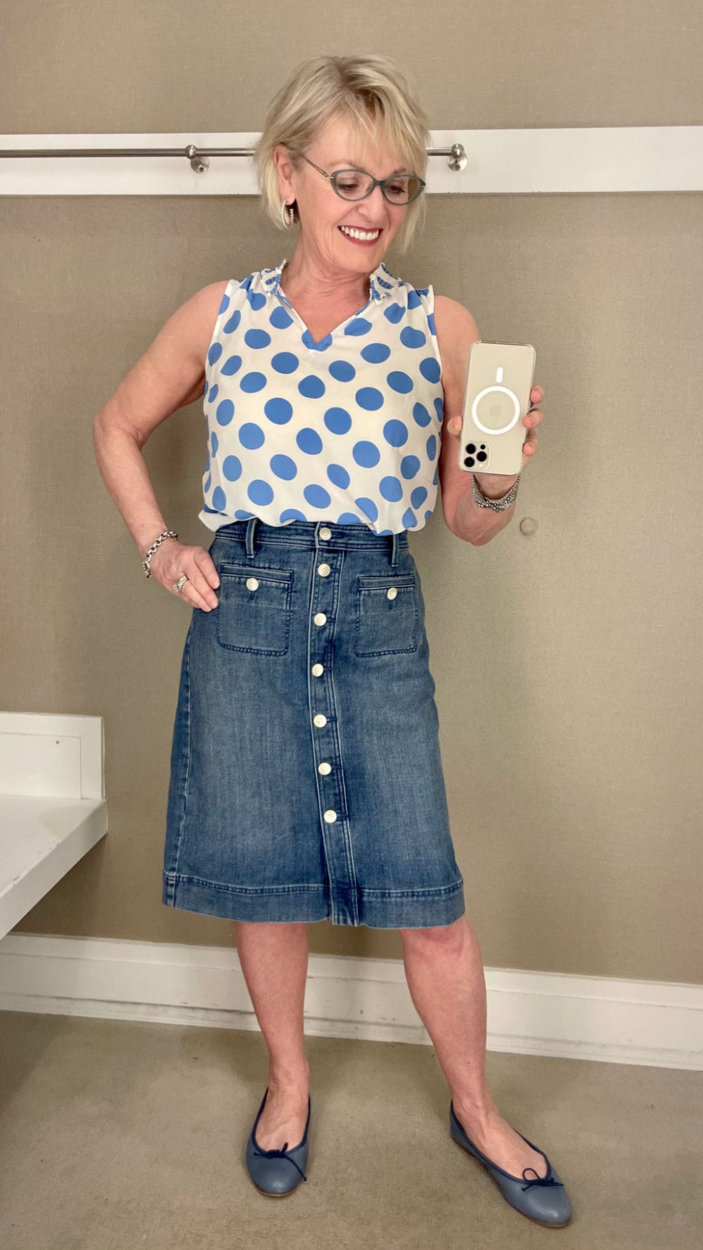 blonde woman wearoing polka dot blouse and denim shirt in dresssing room