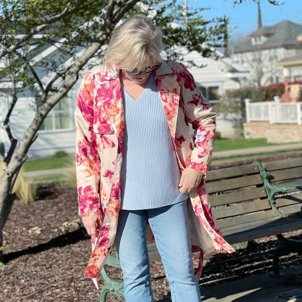 closeup of blue cotton v neck sweater and floral trench