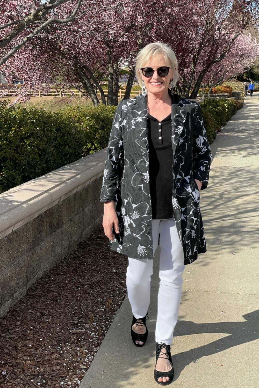 woman walking in white jeans and floral jacket