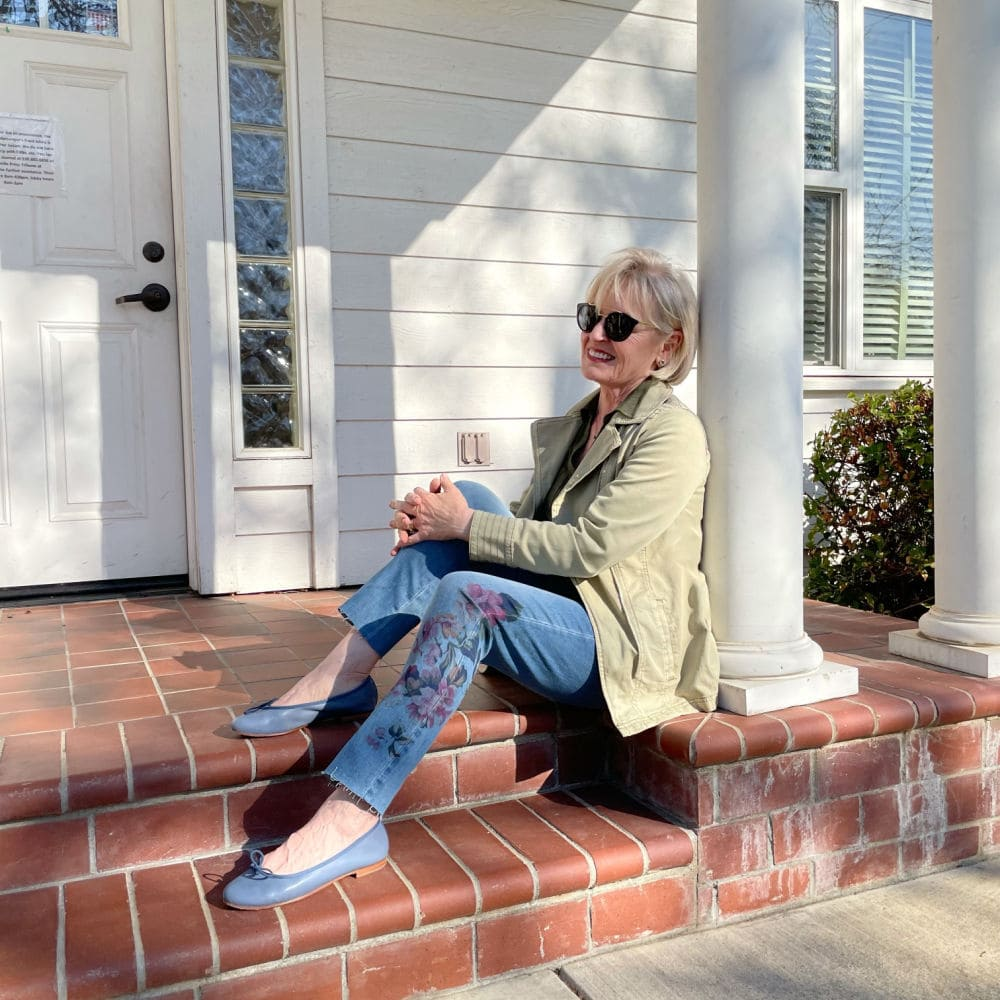 woman sitting on step of white building