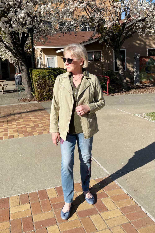 woman walking on brick walkways wearihng green jacket and blue jeans