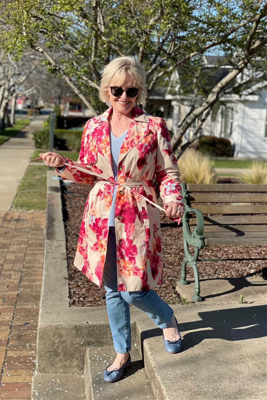 woman cynching belt on floral raincoat