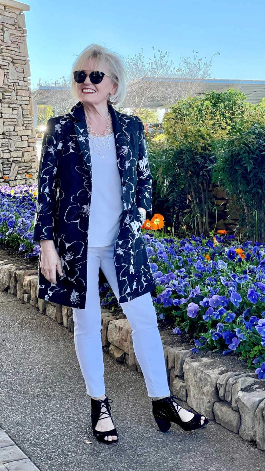 woman wearing a column of white under a floral blazer in black and white