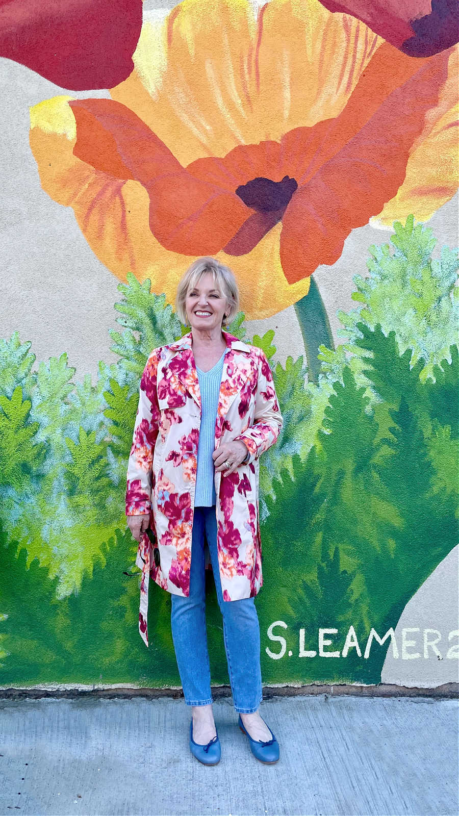 woman standing in front of floral mural wearing floral raincoat