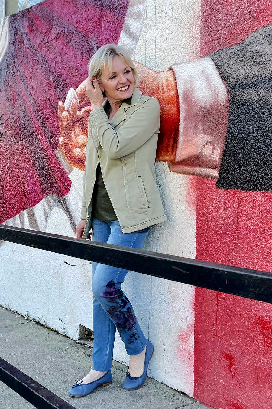 woman leaning against wall with mural of large hand